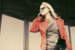 Young fashion business woman in sunglasses calling on cell phone Stock Image