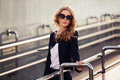 Young fashion business woman in sunglasses on the city street Stock Image