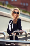 Young fashion business woman in sunglasses on the city street Stock Photo