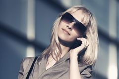 Young fashion business woman talking on cell phone at office building. Young fashion business woman wearing sunglasses talking on cell phone at office building Royalty Free Stock Images