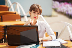 Young fashion business woman using laptop at sidewalk cafe Royalty Free Stock Photo