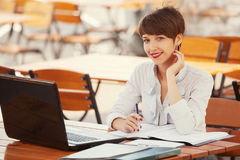 Young fashion business woman using laptop at sidewalk cafe Royalty Free Stock Image