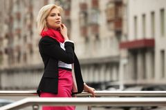 Young fashion business woman walking in city street royalty free stock image