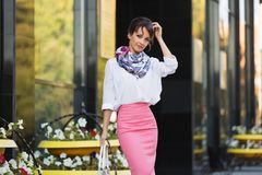 Young fashion business woman in white blouse and pencil skirt. Walking in city street royalty free stock image