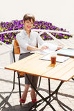 Young fashion business woman working at sidewalk cafe Stock Photos