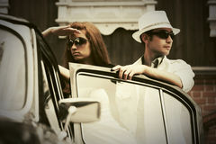 Young fashion couple in conflict next to vintage car. Young fashion men and women in conflict next to vintage car Royalty Free Stock Photography