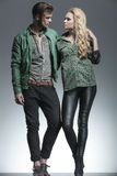 Young fashion couple holding each other. Full length picture of a young fashion couple holding each other, looking away from the camera Royalty Free Stock Photos