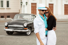 Young fashion couple in love at the retro car. Young fashion men and women at the retro car Stock Image