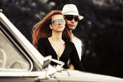 Young fashion couple in love by retro car. Young fashion man and woman in love by retro car Royalty Free Stock Photo