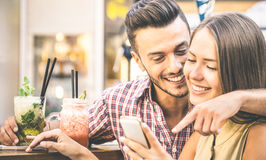 Young fashion couple of lovers playing with mobile smart phone a. T cocktail bar - Relationship love concept with happy boyfriend and girlfriend together Stock Images