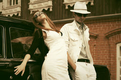 Young fashion couple next to vintage car Royalty Free Stock Images