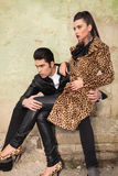 Young fashion couple sitting on old factory ruins Royalty Free Stock Images