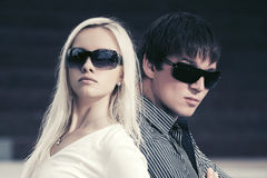 Young fashion couple in sunglasses in a city street. Young fashion couple in sunglasses walking in a city street Royalty Free Stock Images
