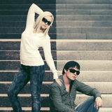 Young fashion couple in sunglasses on the steps Royalty Free Stock Photography