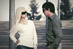 Young fashion couple in sunglasses on the steps Stock Photos