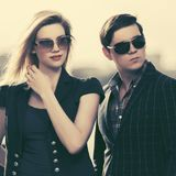 Young fashion couple in sunglasses walking on city street royalty free stock images