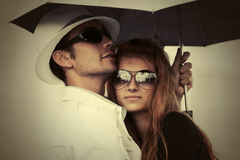 Young fashion couple with umbrella in city street Stock Images