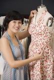 Young fashion designer adjusting dress on the dummy Stock Image