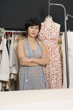 Young fashion designer with arms crossed standing next to a mannequin Stock Photo