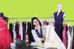 Young fashion designer holds a fabric on studio. Picture of young female fashion designer holding a fabric while sitting in the studio over green screen stock photography