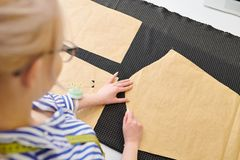 Designer working with sketches. Young fashion designer making white chalk markings of paper patterns on fabric before cutting details for future jacket or royalty free stock images