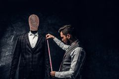 A fashion designer with a measuring tape check the length of the sleeves of a custom made elegant men`s suit in a dark. A young fashion designer with a measuring stock images
