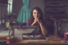 Fashion designer. Young fashion designer sitting at a sewing machine in her workshop, taking a break from work and thinking about new designs Royalty Free Stock Photo