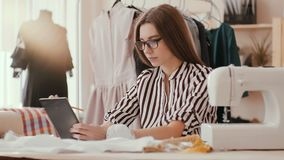 Young fashion designer with tablet searching through new trends in the net