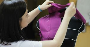 Young fashion designer, tailor and dressmaker adjusting clothes on tailoring mannequin and in studio. Young Woman Fashion Designer Works in Studio. Clothing stock footage