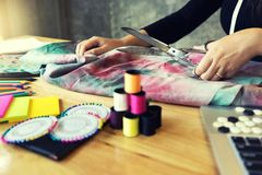 Young fashion designer work with fabric. Cloth on the wood table or graphic designer vintage tone Stock Photos