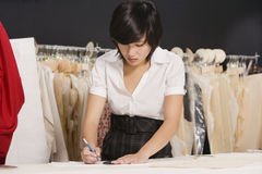 Young fashion designer working at her clothing store Royalty Free Stock Photo