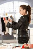 Young fashion designer working in office. Young attractive fashion designer working in bright office, looking at colour samples royalty free stock image