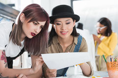 Young fashion designers looking at sketch and discussing. Multiethnic young fashion designers looking at sketch and discussing Royalty Free Stock Photo