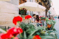Young fashion elegant stylish couple sitting in the summer cafe and holding hands. Beautiful sunny day, red flowers on Royalty Free Stock Photo