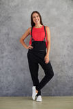 Young fashion girl in black overalls posing isolated on gray bac Royalty Free Stock Photo