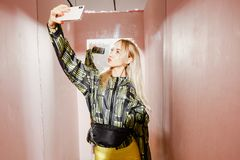 Young fashion girl blogger dressed in a stylish black and yellow jacket and yellow shorts takes a selfie on her. Smartphone in a pink fitting room of the show royalty free stock photo