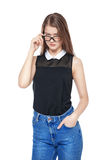 Young fashion girl in jeans and glasses posing isolated Royalty Free Stock Photography