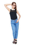 Young fashion girl in jeans and glasses posing isolated Stock Image