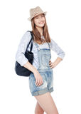 Young fashion girl in jeans overalls and hat posing isolated Stock Photography