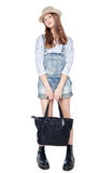 Young fashion girl in jeans overalls and hat posing isolated Royalty Free Stock Photography