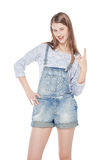 Young fashion girl in jeans overalls with horn gesture isolated Stock Images