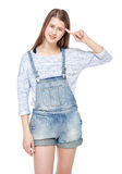 Young fashion girl in jeans overalls making crazy gesture isolat Stock Photography