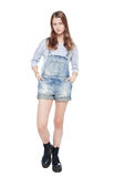 Young fashion girl in jeans overalls posing isolated. On white background stock images