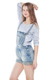 Young fashion girl in jeans overalls posing isolated. On white background royalty free stock photo