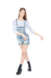Young fashion girl in jeans overalls posing isolated. On white background royalty free stock photography