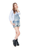 Young fashion girl in jeans overalls posing isolated Royalty Free Stock Photography
