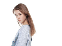 Young fashion girl in jeans overalls posing isolated. On white background stock photography