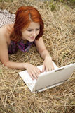 Young  fashion girl with notebook lying at field Royalty Free Stock Photography