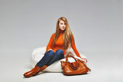 The young fashion girl sitting in trendy clothes in leather boots with bag Royalty Free Stock Image