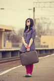 Young fashion girl with suitcase at railways. Stock Photos